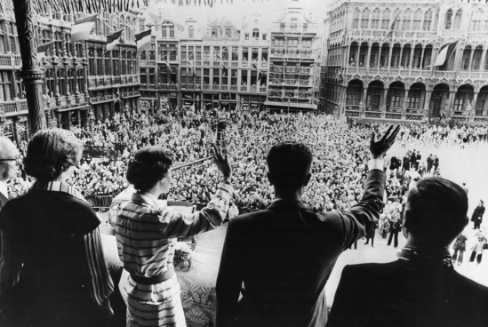 From the balcony of the Brussels City Hall, King Baudouin and Queen Fabiola greet the Belgian people with one heart as the crowd cheers.
